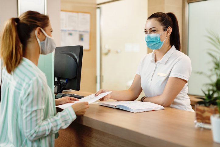 Health spa receptionist and her customer wearing face masks due to coronavirus pandemic..