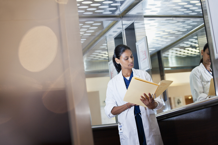 Doctor reviewing medical record in hospital elevator.